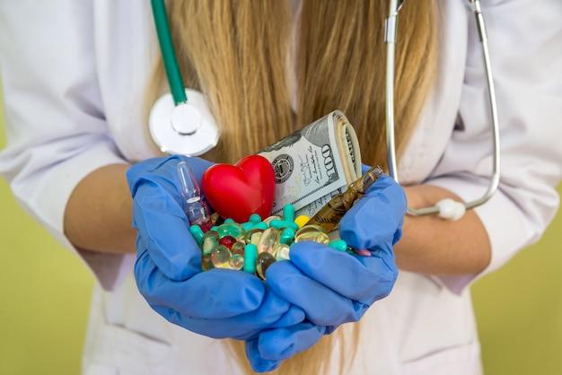 Les mains du médecin tiennent le dollar et différentes pilules isolées sur le vert