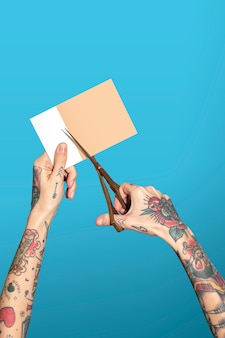 Mains avec du papier de coupe de ciseaux de maintien tatoué