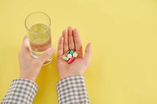 Mains du patient prenant divers suppléments, vitamines et verre d'eau