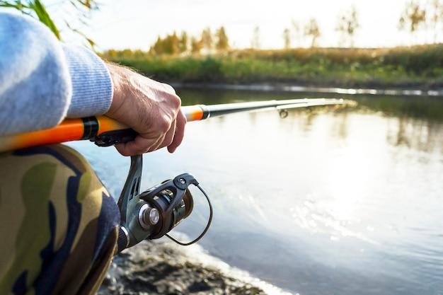 Les mains du pêcheur maintiennent la canne à pêche avec moulinet