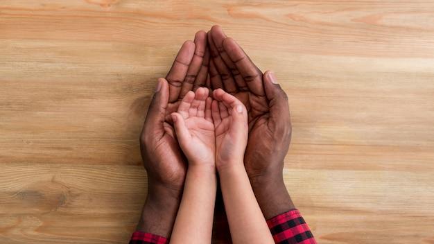 Mains du père et de l'enfant sur la table