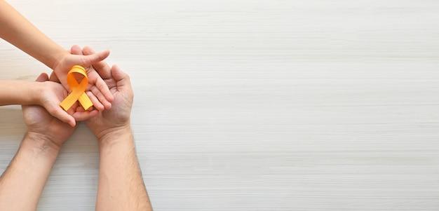 Les mains du père et de l'enfant tiennent un ruban orange sur fond blanc journée mondiale de la sclérose en plaques