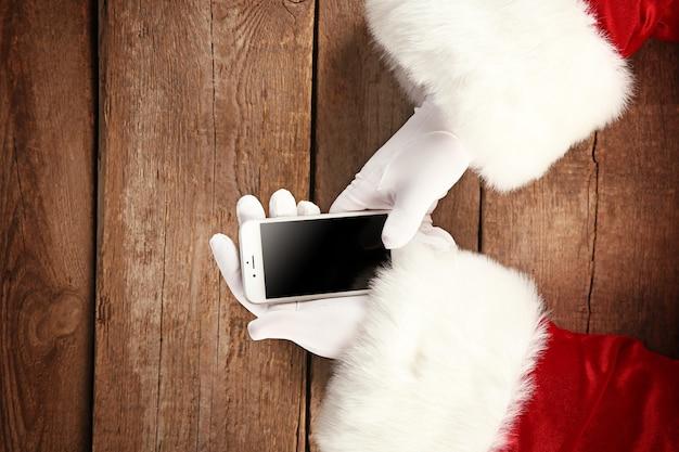 Les mains du père noël avec téléphone portable sur fond de bois, gros plan