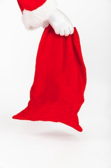 Mains du père noël tenant un sac rouge de cadeaux