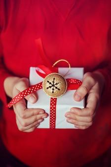 Mains du petit enfant avec un cadeau de noël.