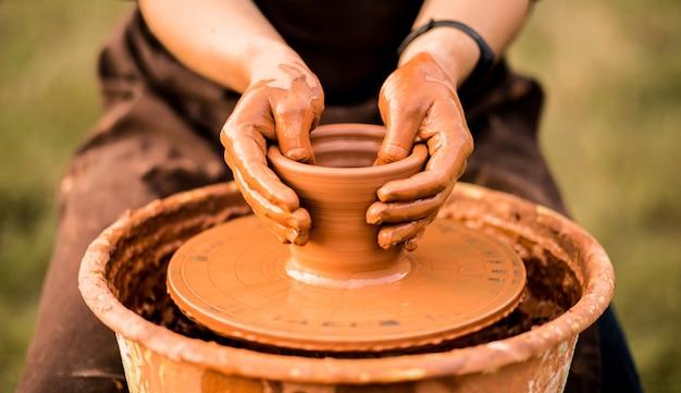 Les mains du potier font un pot en céramique sur la mise au point sélective extérieure d'un tour de poterie