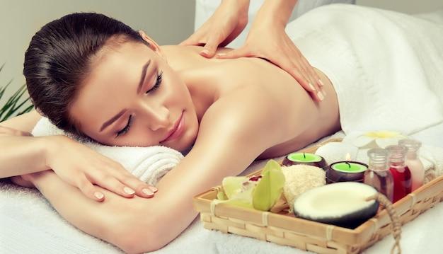 Les mains du spécialiste du massage font un massage sur le dos d'une femme jeune et attrayante