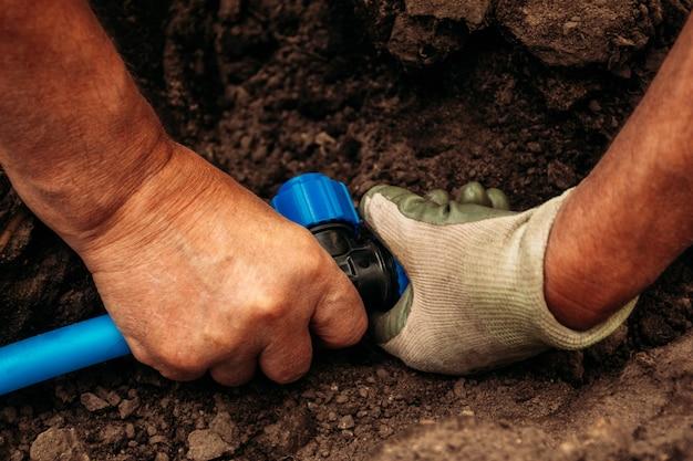 Les mains du système d'irrigation fonctionnant avec un tuyau de raccordement