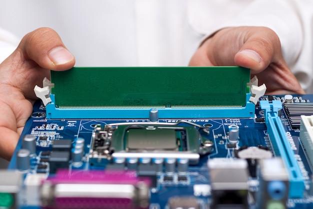 Les mains du technicien installant la mémoire utilisateur sur une carte mère d'ordinateur