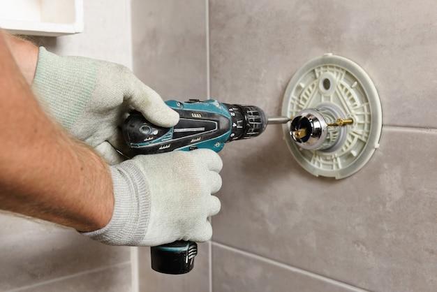 Les mains du travailleur montent un robinet intégré.