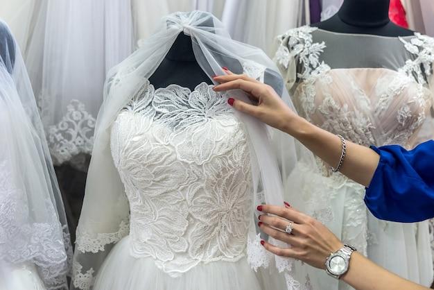 Les mains du vendeur corrigent le voile de mariée sur mannequin en salon