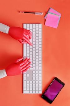 Mains et dummy tapant sur le clavier de l'ordinateur avec un téléphone mobile à côté