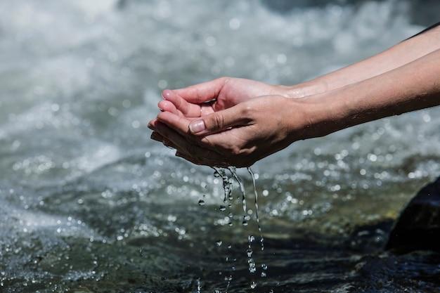 Mains avec de l'eau propre du ruisseau de montagne bouillonnant