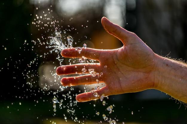 Mains avec éclaboussures d'eau, rétro-éclairé par le soleil du soir.