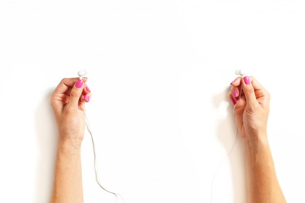 Mains avec des écouteurs sur fond blanc