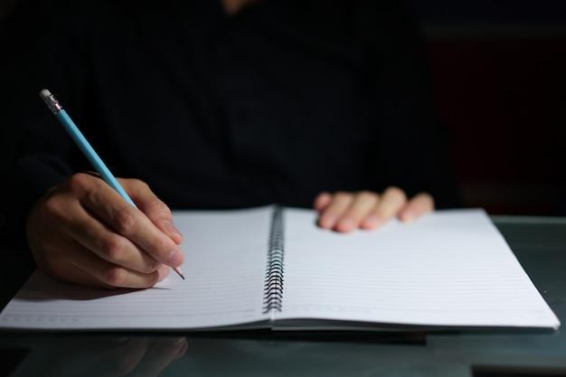 Mains écrivant sur le bloc-notes en faisceau lumineux