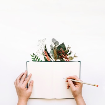 Mains écrivant dans le livre ouvert et laisse