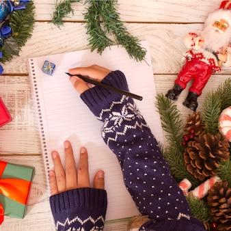 Mains écrivant une lettre au père noël sur la farine en bois près de boîtes de cadeau de noël