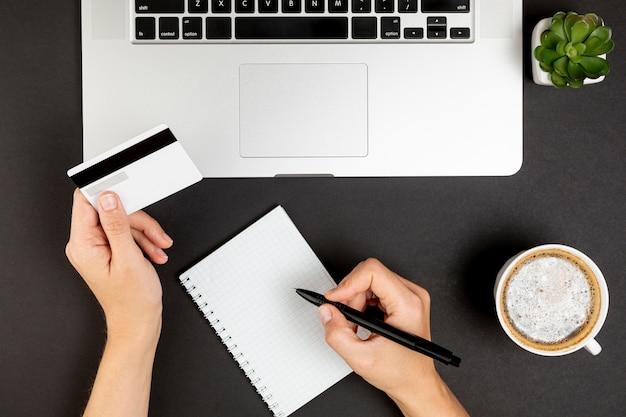 Mains écrivant et tenant une carte de crédit