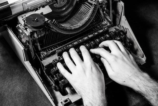 Mains écrivant sur une vieille machine à écrire