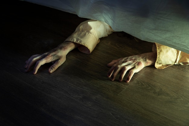 Mains effrayantes de zombie sous le lit