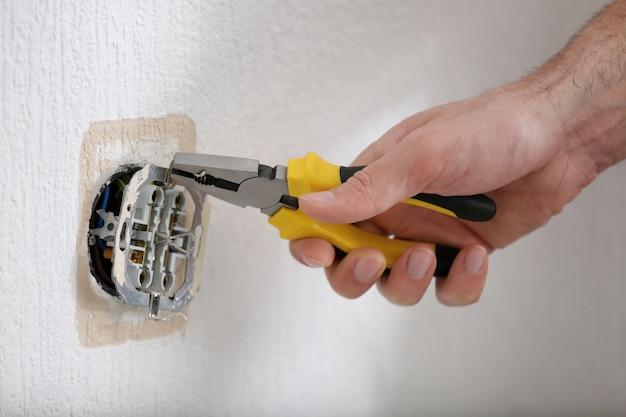 Mains d'électricien installant la prise, plan rapproché