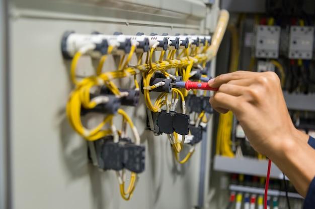 Mains d'électricien testant le courant électrique dans le panneau de commande.