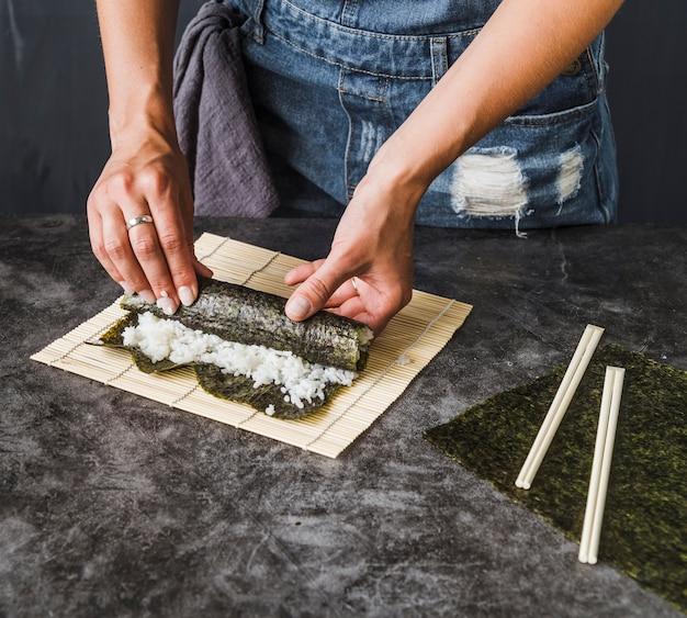 Mains emballant des algues grillées