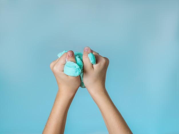 Les mains de l'enfant agrippent une bave couleur ciel contre le ciel. le concept de faire le ciel de vos propres mains.