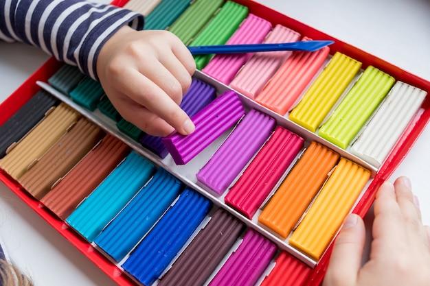 Les mains de l'enfant avec de l'argile colorée. tout-petit jouant et créant des jouets à partir de pâte à modeler, modelage de moulage
