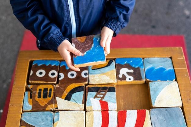 Les mains de l'enfant complètent un puzzle d'artisan composé de cubes en bois.