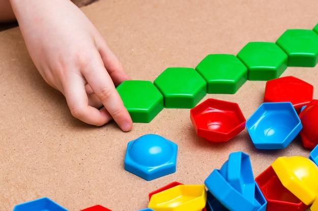 Les mains de l'enfant empilent des détails de mosaïque de couleur dans une rangée