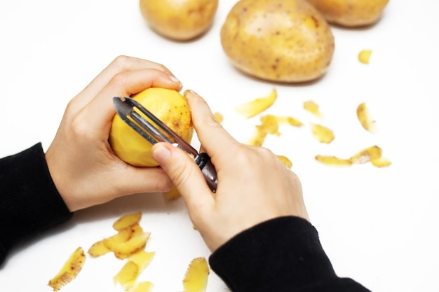 Mains d'un enfant éplucher une pomme de terre avec un éplucheur à la cuisine, coup de main. gros plan photo