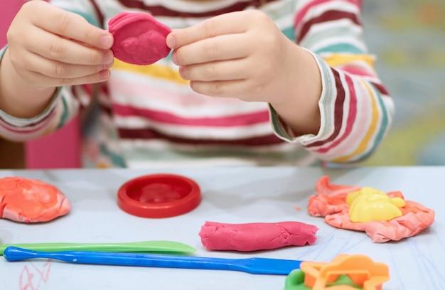 Mains d'enfant jouant avec de l'argile colorée. pâte à modeler. pâte à modeler, quarantaine à distance sociale covid-19, auto-isolement, concept d'éducation en ligne, enseignement à domicile. petite fille à la maison, jardin d'enfants fermé.