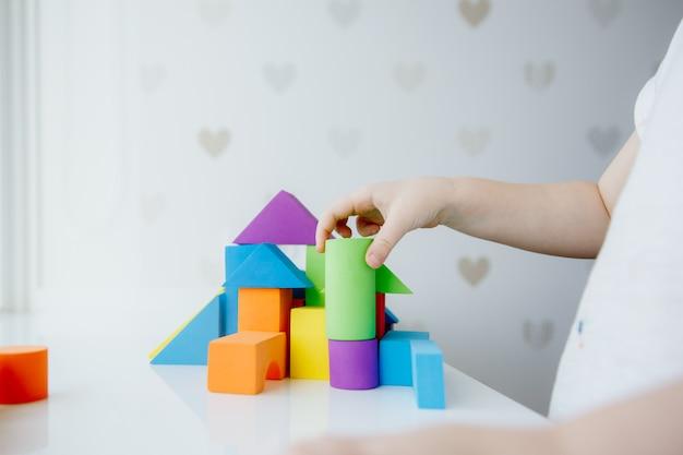 Mains d'enfant jouant avec des briques en bois colorées sur l'onglet blanc