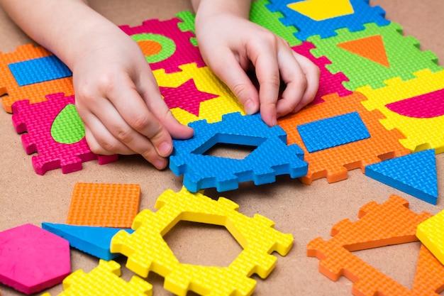 Les mains de l'enfant mettent l'objet dans un puzzle de couleur