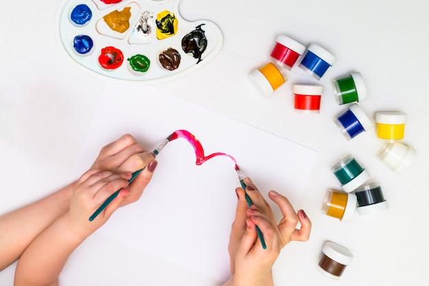 Les mains de l'enfant peignant un coeur