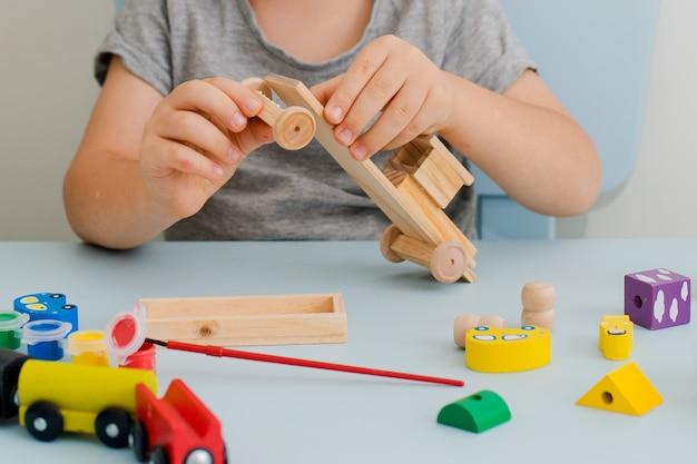 Les mains d'un enfant peignent une machine en bois