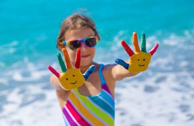 Mains d'enfant peintes avec des peintures sur la mer. mise au point sélective. enfant.