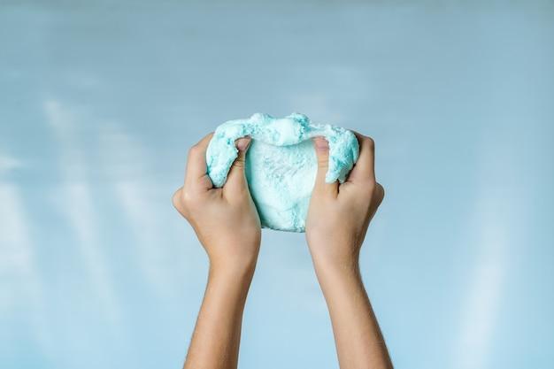 Les mains de l'enfant pétrissent une bave bleue sur fond bleu. le concept de faire le ciel de vos propres mains.