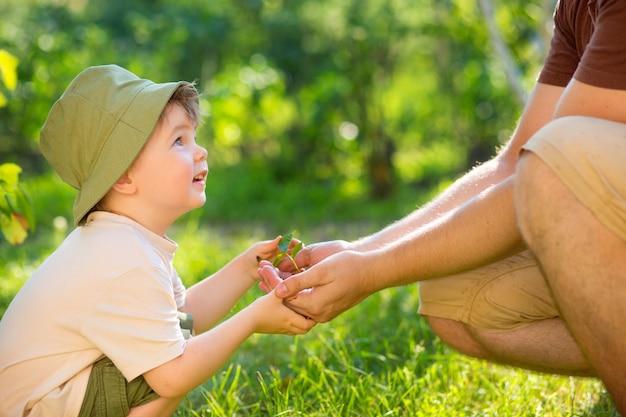Mains d'un enfant prenant une plante des mains d'un homme. concept eco jour de la terre