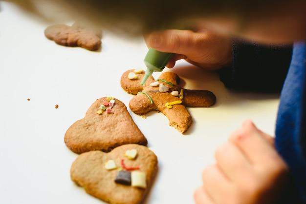 Mains d'enfant préparant des biscuits de pain d'épice maison avec des décorations colorées.