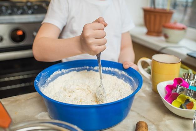 Les mains d'un enfant qui mélange la pâte. cuisiner à la maison