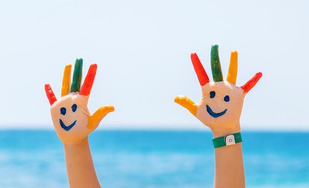 Sur les mains de l'enfant, un sourire avec des peintures sur la mer