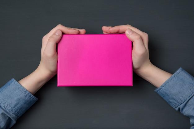 Les mains de l'enfant tenant une boîte cadeau rose sur fond noir. vue de dessus.