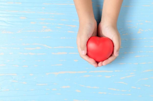 Mains d'enfant tenant coeur rouge sur bois bleu