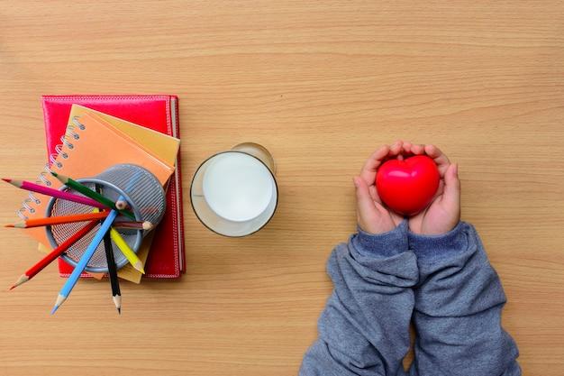 Mains d'enfant tenant un coeur rouge et un cahier avec un crayon de couleur et du lait sur une table en bois.