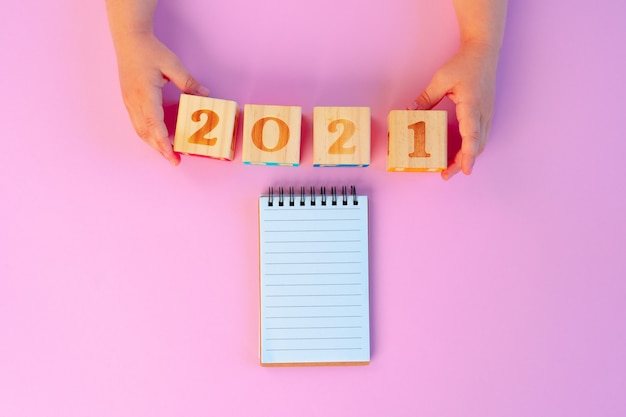 Mains d'un enfant tenant des cubes en bois de l'année 2021 sur fond rose