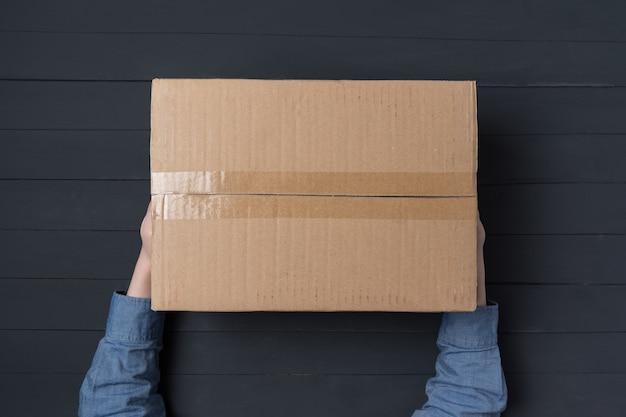 Mains d'enfant tenant une grande boîte en carton. livraison de colis à domicile.