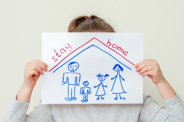 Mains d'enfant tenant une photo de la silhouette de la famille sous le toit et les mots restez à la maison couvrant son visage sur fond jaune. enfants dans le concept de quarantaine.